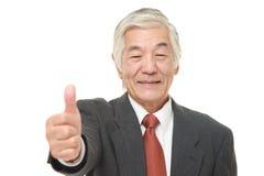 L'homme d'affaires japonais supérieur avec des pouces lèvent le geste Image libre de droits
