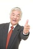 L'homme d'affaires japonais supérieur avec des pouces lèvent le geste Photo libre de droits