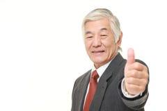 L'homme d'affaires japonais supérieur avec des pouces lèvent le geste Photographie stock libre de droits