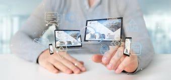 L'homme d'affaires jugeant des dispositifs a relié aux multimédia de nuage un Ne photo stock