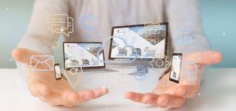 L'homme d'affaires jugeant des dispositifs a relié aux multimédia de nuage un Ne image stock