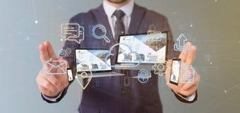 L'homme d'affaires jugeant des dispositifs a relié aux multimédia de nuage un Ne photos libres de droits