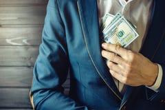 L'homme d'affaires, le membre ou le dirigeant met un paiement illicite dans sa poche Images stock