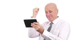 L'homme d'affaires a lu de bonnes nouvelles sur le comprimé et fait le geste de main enthousiaste banque de vidéos