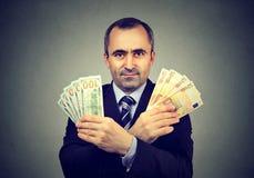 L'homme d'affaires mûres avec l'euro et le dollar encaissent des billets de banque Photos libres de droits