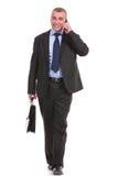 L'homme d'affaires marche avec la serviette et au téléphone Photographie stock