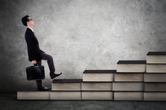 L'homme d'affaires marche sur l'escalier de livres Photographie stock