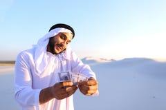 L'homme d'affaires masculin musulman parle au téléphone et partage des actualités avec des élém. Images libres de droits
