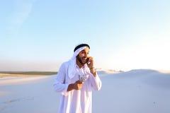 L'homme d'affaires masculin musulman parle au téléphone et partage des actualités avec des élém. Images stock