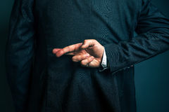 L'homme d'affaires menteur tenant des doigts a croisé derrière le sien de retour Images stock