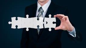 L'homme d'affaires met des puzzles virtuels Le concept d'affaires Préparation pour l'écriture du texte Photos libres de droits
