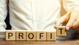 L'homme d'affaires met les blocs en bois avec le bénéfice de mot Le bilan financier de la société pendant une certaine période pr photo stock