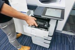 L'homme d'affaires a mis la cartouche d'encre dans l'imprimante Image libre de droits