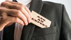 L'homme d'affaires montrant une lecture en bois de carte demandent à un expert Image stock