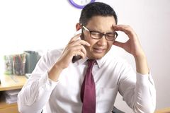L'homme d'affaires montre l'expression triste et choquée, recevant la mauvaise nouvelle au téléphone images libres de droits