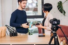 L'homme d'affaires montre ses marchandises à une présentatrice photographie stock libre de droits