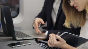 L'homme d'affaires multi-ethnique explique les détails de la présentation à son secrétaire féminin dans l'avion banque de vidéos