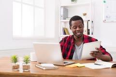L'homme d'affaires noir dans le bureau occasionnel, travaillent chacun des deux sur l'ordinateur portable et le comprimé Photographie stock