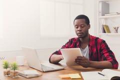 L'homme d'affaires noir dans le bureau occasionnel, travaillent chacun des deux sur l'ordinateur portable et le tabl Images stock