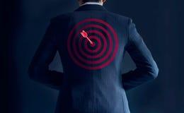 L'homme d'affaires obtiennent le succès avec la flèche rouge sur la cible au fond de son costume Photographie stock libre de droits