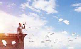 L'homme d'affaires ou le directeur annonçant quelque chose dans des avions de haut-parleur et de papier volent autour Images stock