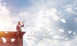 L'homme d'affaires ou le directeur annonçant quelque chose dans des avions de haut-parleur et de papier volent autour Photos libres de droits