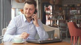 L'homme d'affaires parle au téléphone au café