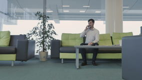 L'homme d'affaires parle au téléphone et regarde la piste banque de vidéos