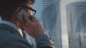 L'homme d'affaires parle du smartphone sur la rue Affaires sur l'aller clips vidéos