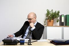 L'homme d'affaires pense, alors qu'il se plie au-dessus d'un dossier Image stock