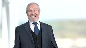 L'homme d'affaires plus âgé rit, fond brouillé banque de vidéos
