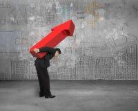 L'homme d'affaires portant le grand signe rouge de flèche avec le concept d'affaires font Image stock