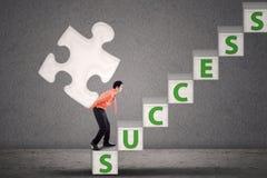 L'homme d'affaires portent le morceau de puzzle sur des escaliers de succès Image stock