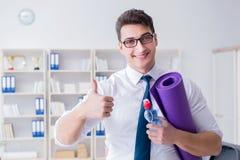 L'homme d'affaires préparant pour aller s'exercer dans le gymnase photographie stock libre de droits