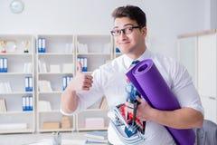 L'homme d'affaires préparant pour aller s'exercer dans le gymnase Image libre de droits