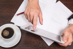 L'homme d'affaires réussi emploie l'Internet sur sa tablette, dans le lieu de travail sont les documents avec des programmes et u image libre de droits