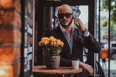 L'homme d'affaires réussi parle par le téléphone tout en se reposant au coffeeshop photos libres de droits