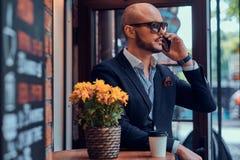 L'homme d'affaires réussi parle par le téléphone tout en se reposant au coffeeshop photographie stock libre de droits