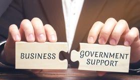 L'homme d'affaires rassemble des puzzles avec les affaires de mots et le soutien gouvernemental ALLÉGEMENT FISCAL D'IMPÔTS Protec photo libre de droits