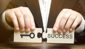 L'homme d'affaires rassemble des puzzles en bois principaux au succès Concept d'atteindre le but, surmontant des difficultés, occ photos stock