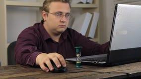 L'homme d'affaires regardant un ordinateur portable et un bras renverse le sablier banque de vidéos