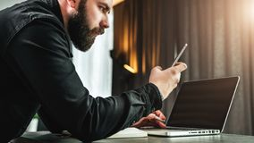 L'homme d'affaires regarde l'écran du smartphone, lit le message tout en travaillant à l'ordinateur portable Le jeune entrepreneu photographie stock