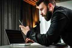L'homme d'affaires regarde l'écran du smartphone, lit le message tout en travaillant à l'ordinateur portable Le jeune entrepreneu photos stock