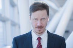 L'homme d'affaires regarde l'appareil-photo avec d'expression étrange Photographie stock libre de droits