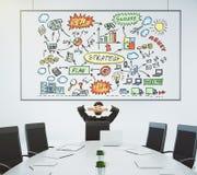 L'homme d'affaires regarde l'affiche avec le plan et le confere d'affaires photographie stock