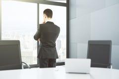 L'homme d'affaires regarde la fenêtre dans le bureau avec de grandes fenêtres et images libres de droits