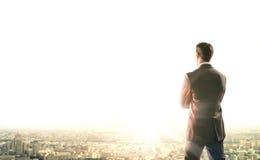L'homme d'affaires regarde le lever de soleil dans la ville photos libres de droits