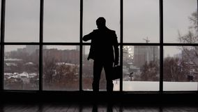 L'homme d'affaires regarde le temps sur la montre-bracelet dans le bureau près de la fenêtre banque de vidéos