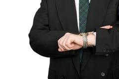 L'homme d'affaires regarde le temps sur sa montre-bracelet. photographie stock