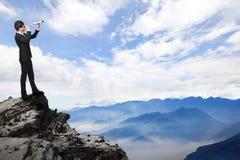 L'homme d'affaires regarde par le télescope sur la montagne Images libres de droits